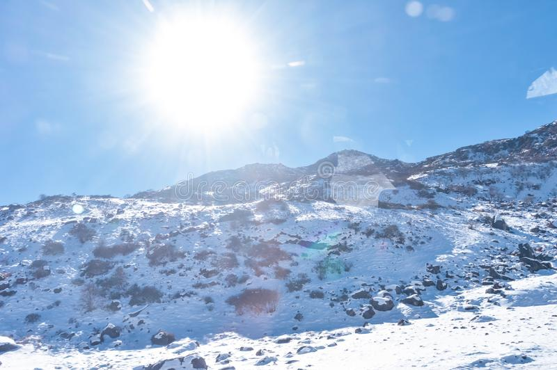 Sun on top of snow cover himalaya range. Frozen Rocky peak filled with deep snow illuminate rising sunlight in frosty winter day. Time. Blue clear sky. No Cloud stock image