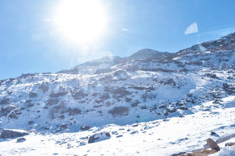 Sun on top of snow cover himalaya range. Frozen Rocky peak filled with deep snow illuminate rising sunlight in frosty winter day. Time. Blue clear sky. No Cloud stock images