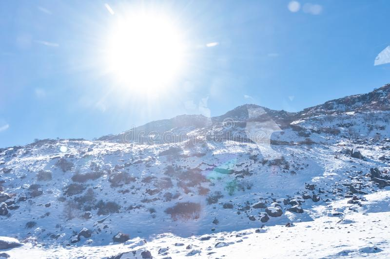 Sun on top of snow cover himalaya range. Frozen Rocky peak filled with deep snow illuminate rising sunlight in frosty winter day. Time. Blue clear sky. No Cloud royalty free stock photos