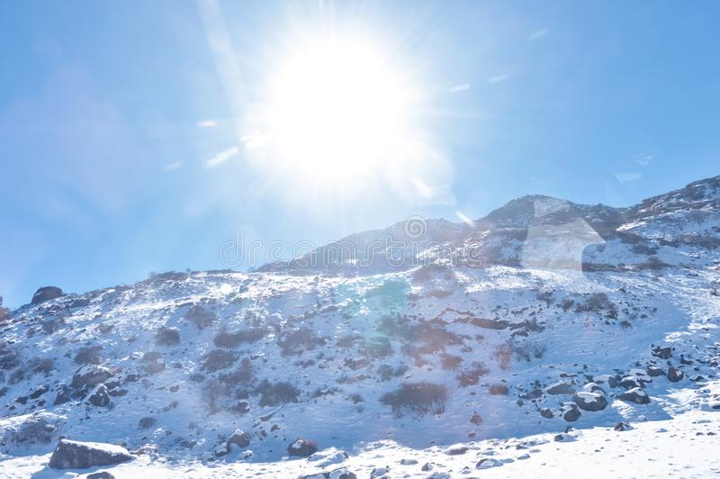Sun on top of snow cover himalaya range. Frozen Rocky peak filled with deep snow illuminate rising sunlight in frosty winter day. Time. Blue clear sky. No Cloud royalty free stock photography