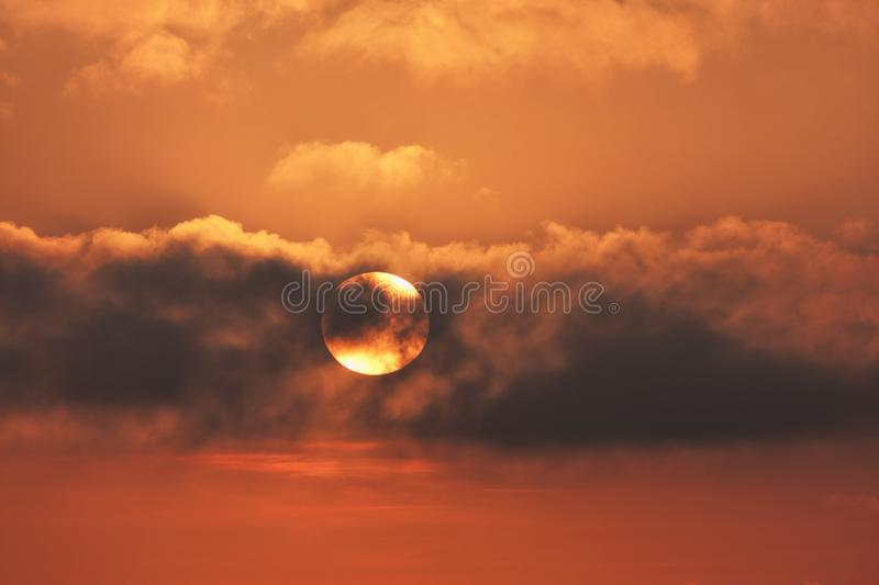 The sun towards the sunset in the clouds spreads orange light stock image