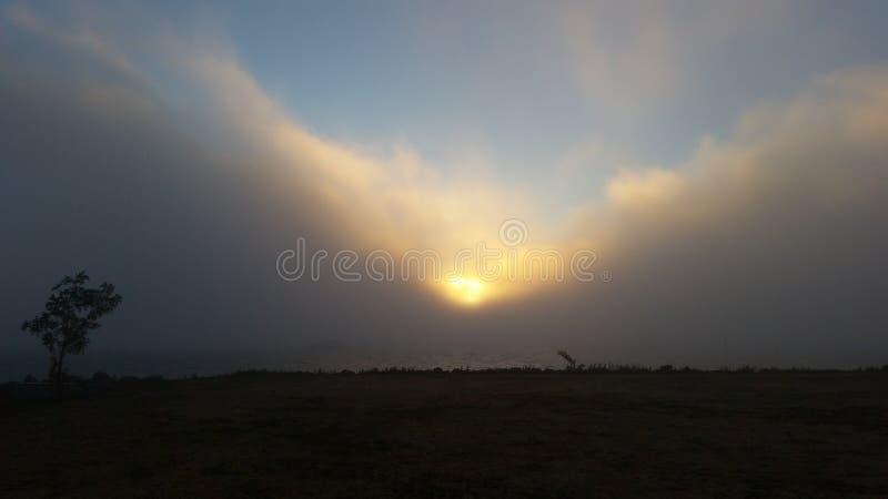 Sun a través de las nubes y de menos mar fotos de archivo libres de regalías