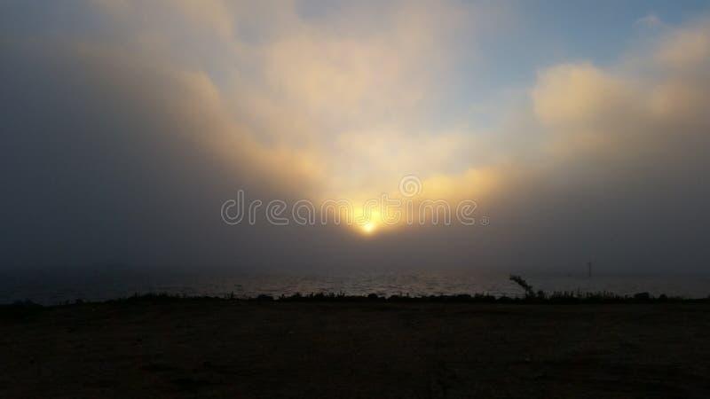 Sun a través de las nubes y del mar imagen de archivo