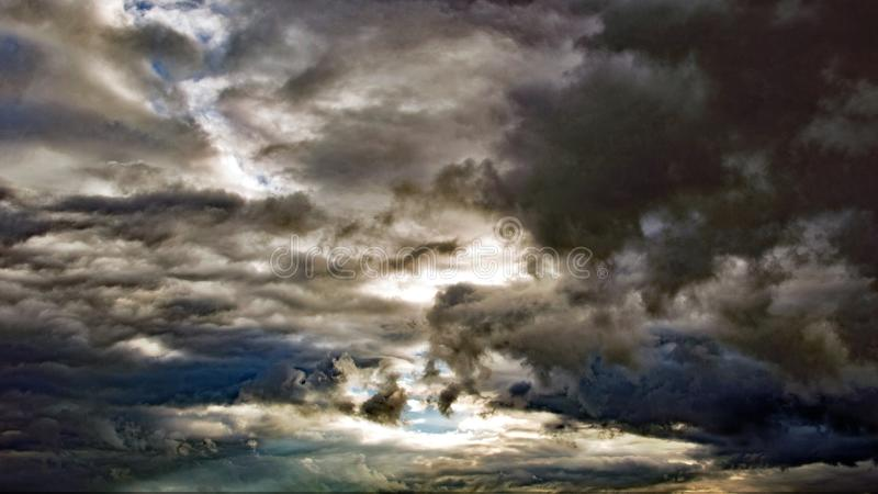 Sun trying to peek out of dark clouds. In the evening the sun tries to peek out the clouds stock photography
