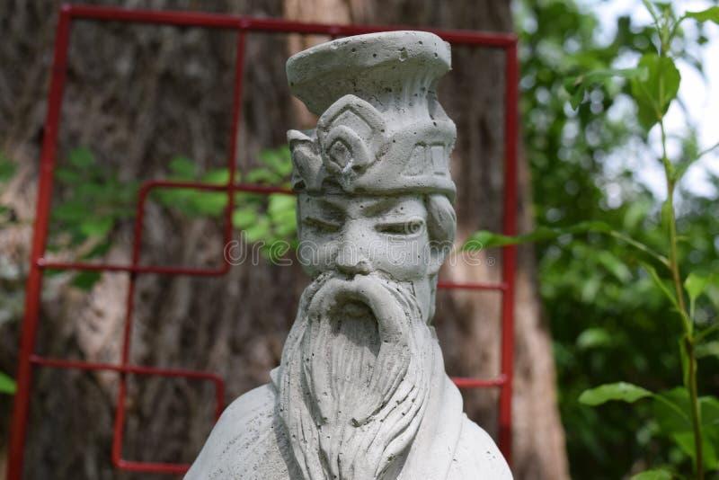 Sun Tzu-Statue vor roter Gartenlaube stockbild