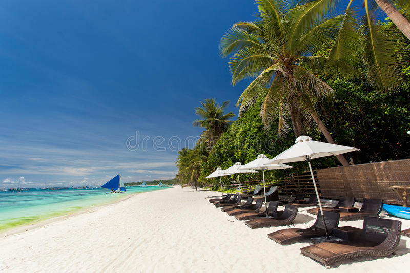 Sun umbrellas and beach chairs on tropical coastline royalty free stock photo