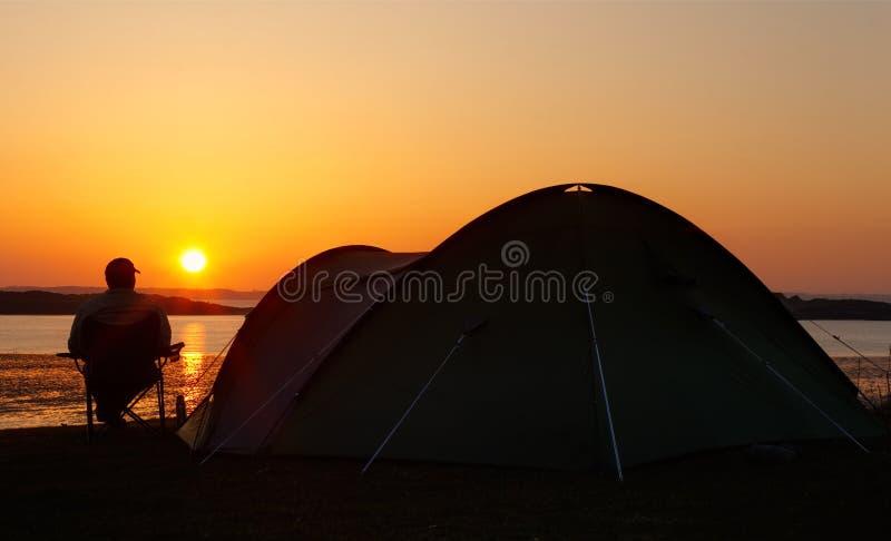 Solnedgångar bak campare och tenten royaltyfria bilder