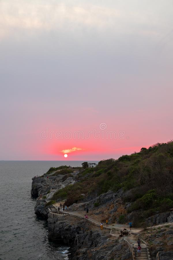 sun was setting into the sea with the foreground is an island jutting into the sea stock photo