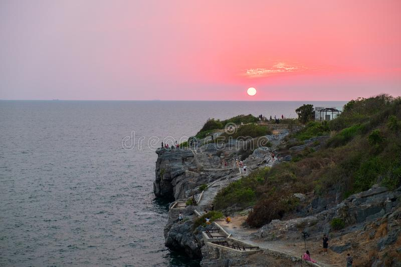 sun was setting into the sea with the foreground is an island jutting into the sea royalty free stock image