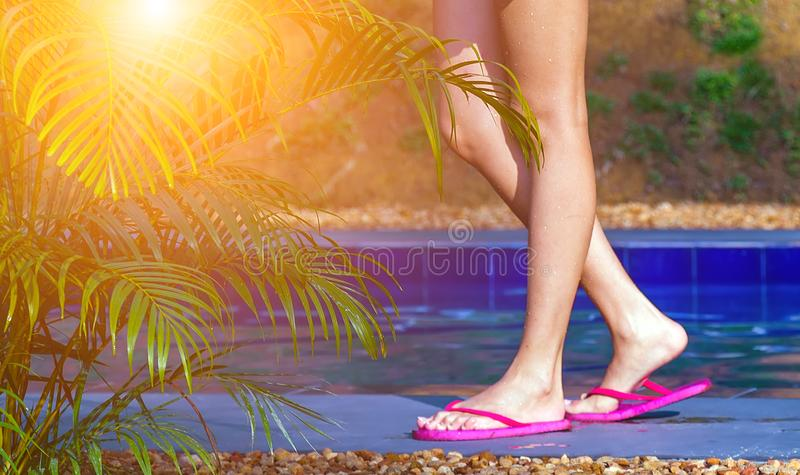 Sun woman skin care wellness spa resort. Sun skin care wellbeing wellness long tanned woman legs receiving massage in spa, woman relaxing in swimming pool at spa royalty free stock photography