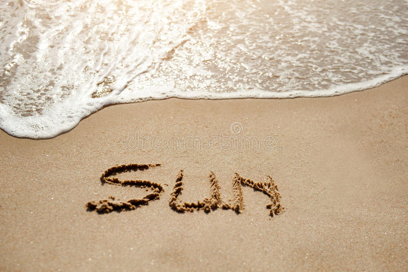 Sun written on the sand beach near sea - holiday relax concept stock image