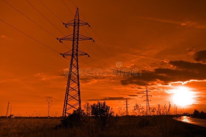 Sun y electricidad - las líneas eléctricas se elevan en la puesta del sol foto de archivo
