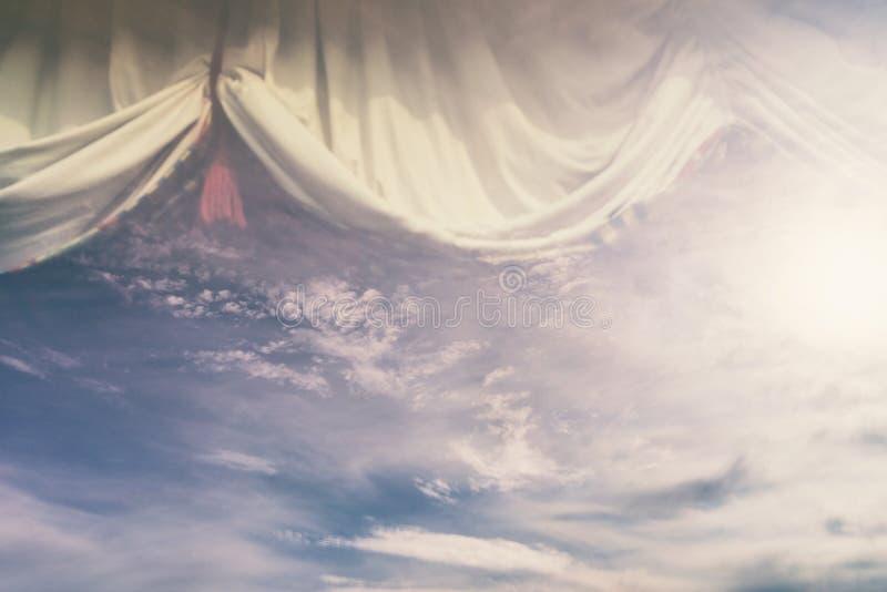 Sun y nubes en la reflexión con las cortinas foto de archivo