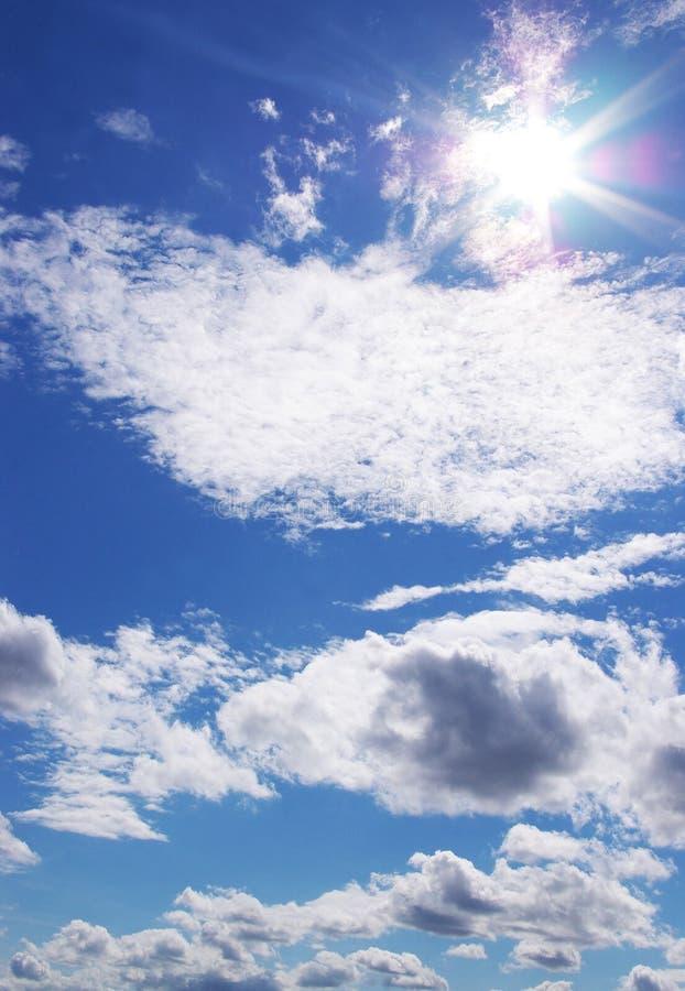 Sun y nubes en un cielo azul fotografía de archivo