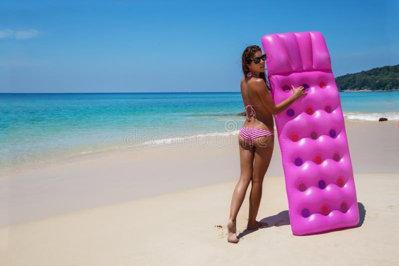 Sunbath delgado joven de la mujer con el colchón de aire en la playa tropical foto de archivo