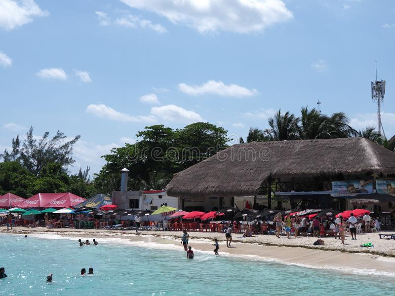 Sunbath places under umbrellas and palm trees on tropical sandy turtle beach with tourists in Cancun city in Mexico. CANCUN, MEXICO NORTH AMERICA on MARCH 2018 stock photo