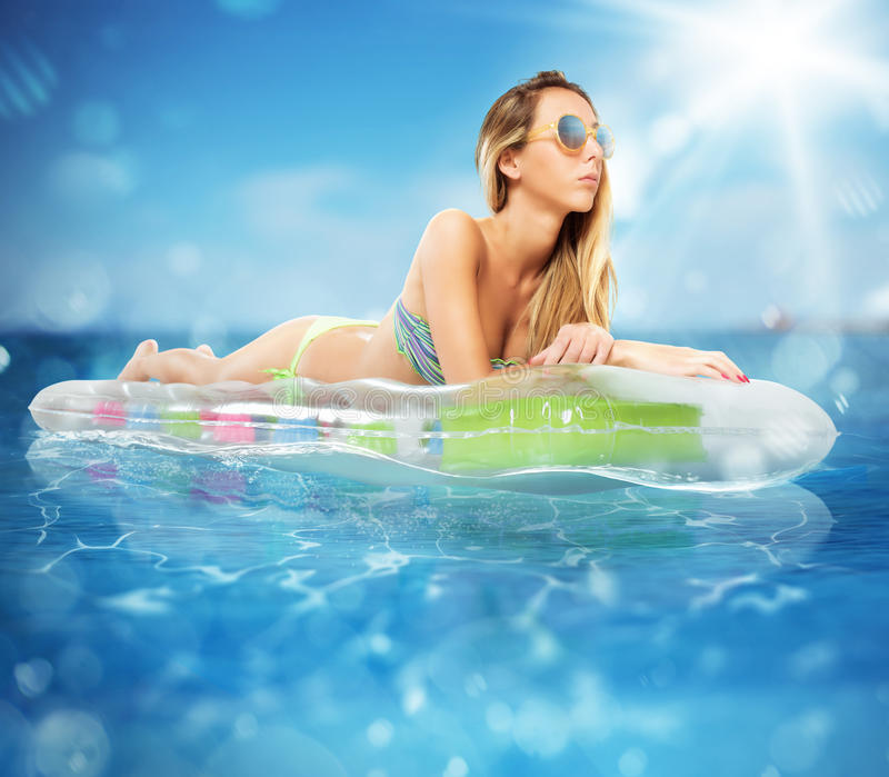 Sunbathe on airbed. Sunbathe on an airbed in the sea stock photography