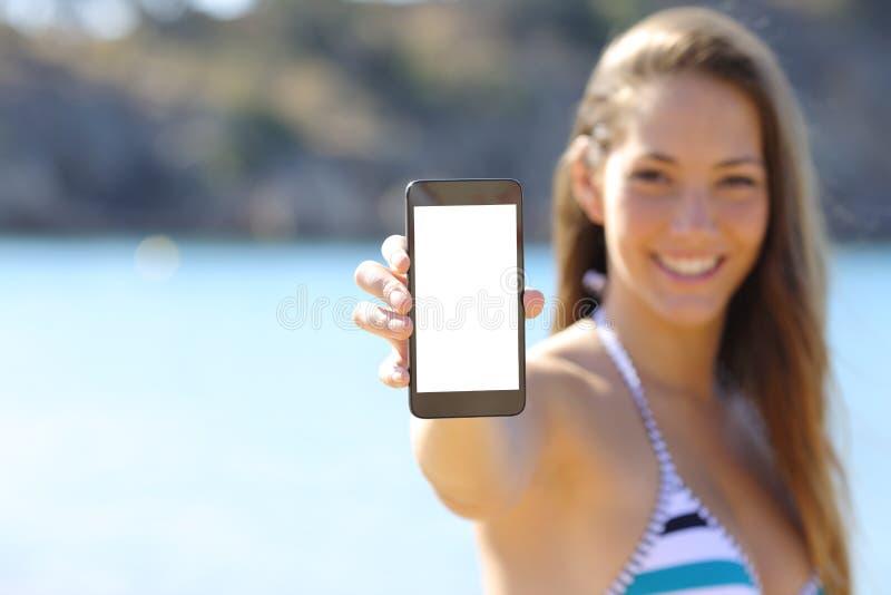Sunbather показывая пустой экран телефона на пляже