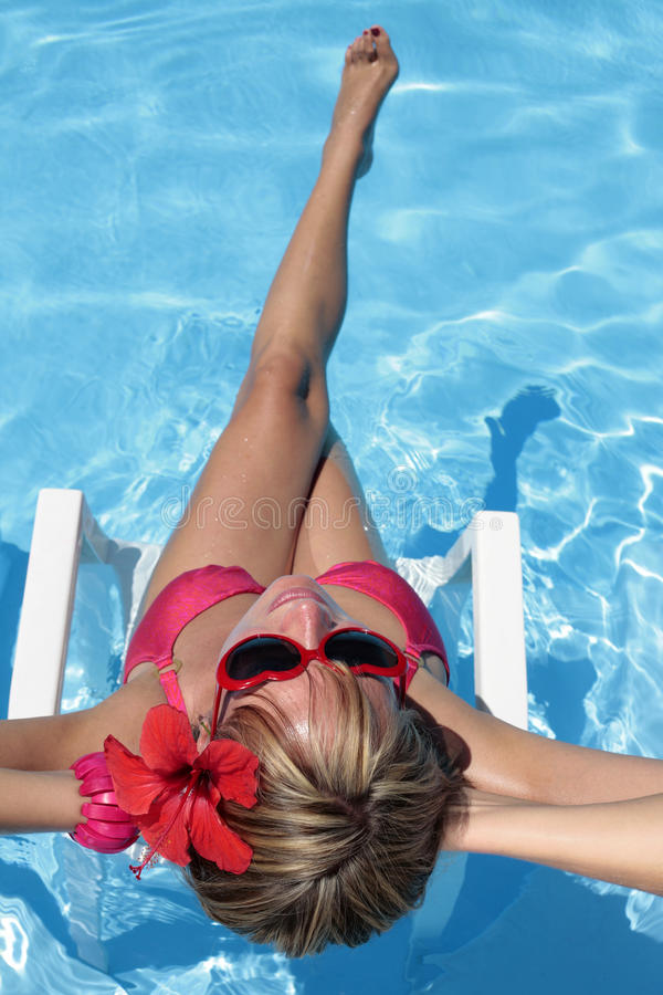 Sunbather in einem blauen Pool stockfotografie