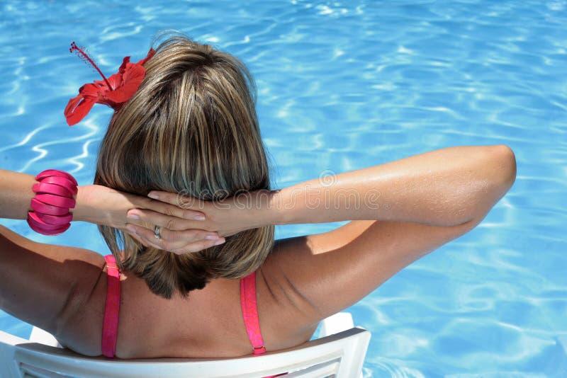 Sunbather in einem blauen Pool stockfotos