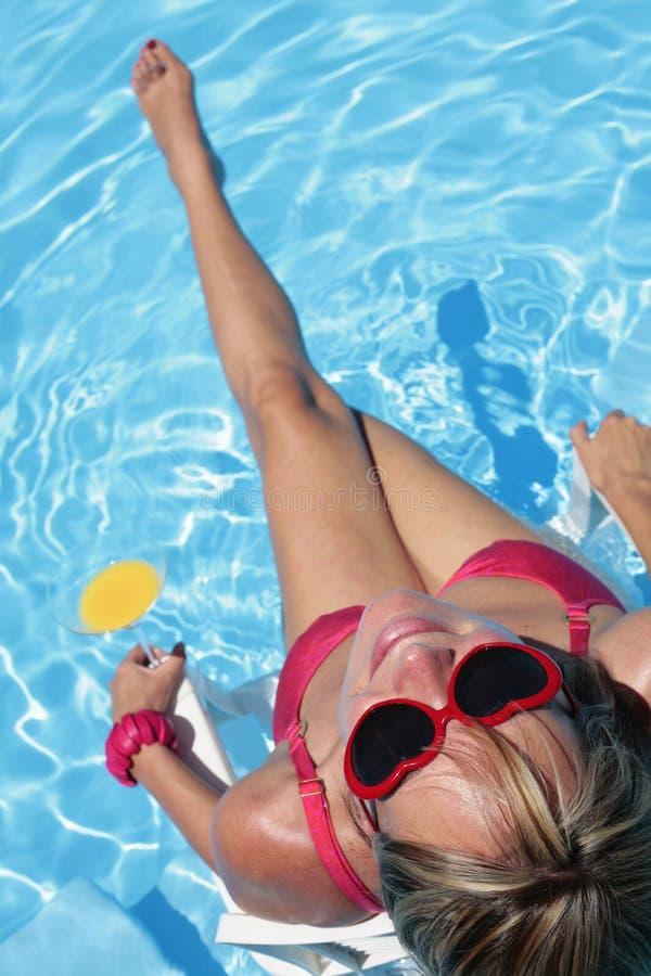 Sunbather in einem blauen Pool stockbilder