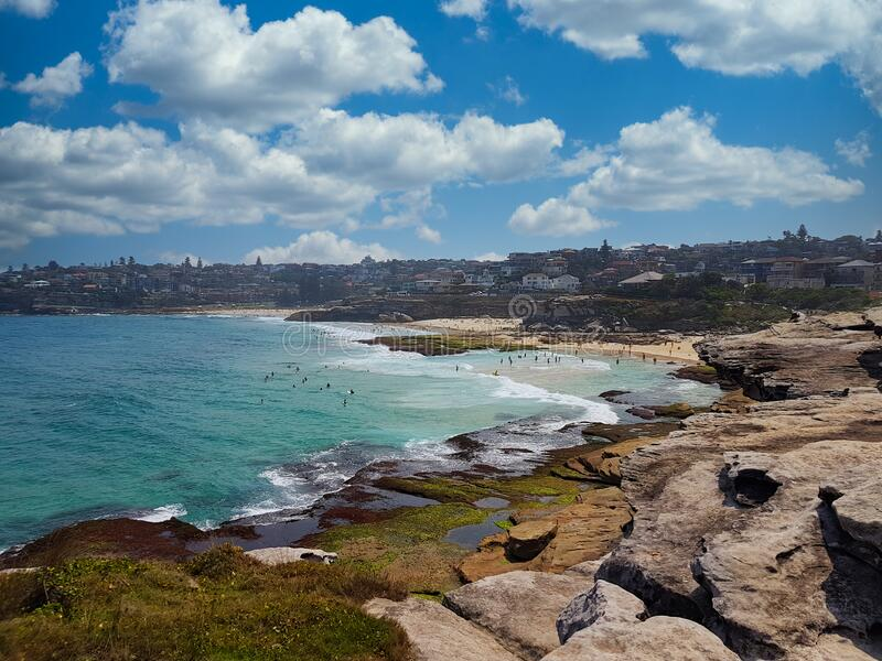 Sunbathers and swimmers on the Tamarama Beach in Sydney, Australia.  stock photo