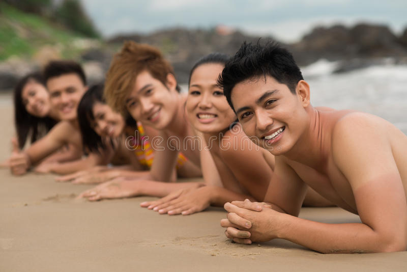 Sunbathing. Portrait of a group of friends sun bathing together on the beach stock photo