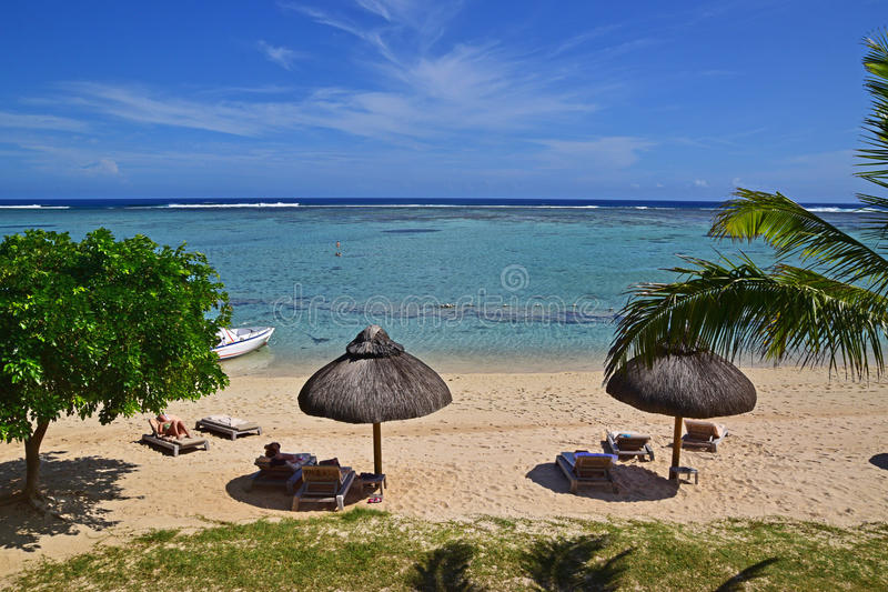 Sunbathing vacation at a luxury resort in Le Morne Beach, Mauritius. The picture is showing tourists sunbathing on deck chairs with thatched roof hut, boat on stock image