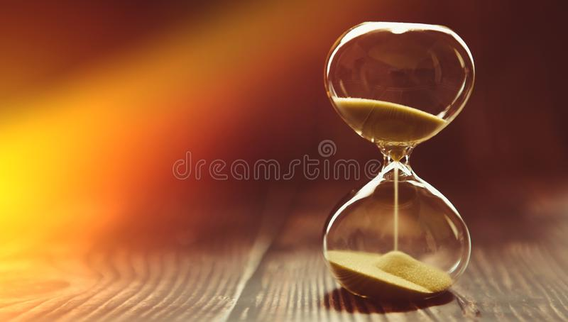 The sunbeam penetrates the hourglass, symbolizing the beginning of time or the final time. Clock on a wooden background royalty free stock images