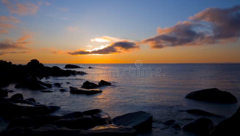 Sunbeam superior da nuvem à água à pedra imagem de stock royalty free