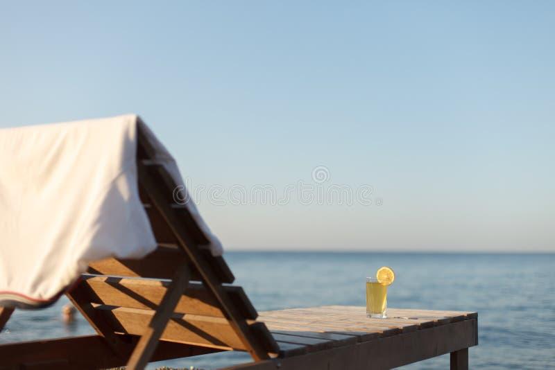 Sunbed con el polo y el vidrio de la bebida fría sobre él en la playa del mar imágenes de archivo libres de regalías