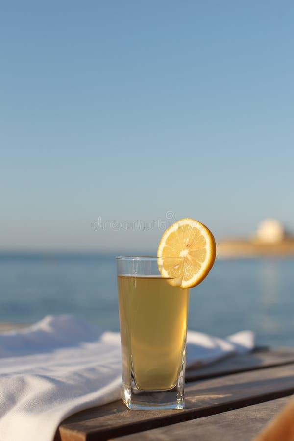 Sunbed con el polo y el vidrio de la bebida fría sobre él en la playa del mar fotos de archivo libres de regalías
