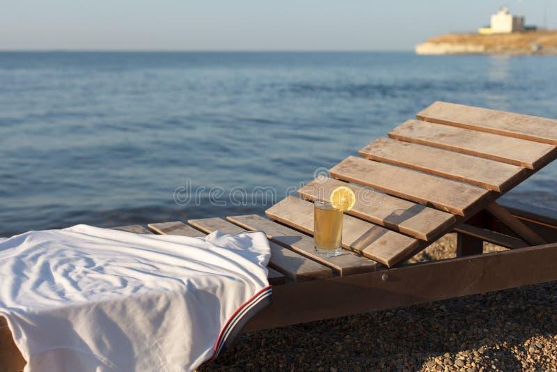 Sunbed con el polo y el vidrio de la bebida fría sobre él en la playa del mar fotografía de archivo libre de regalías
