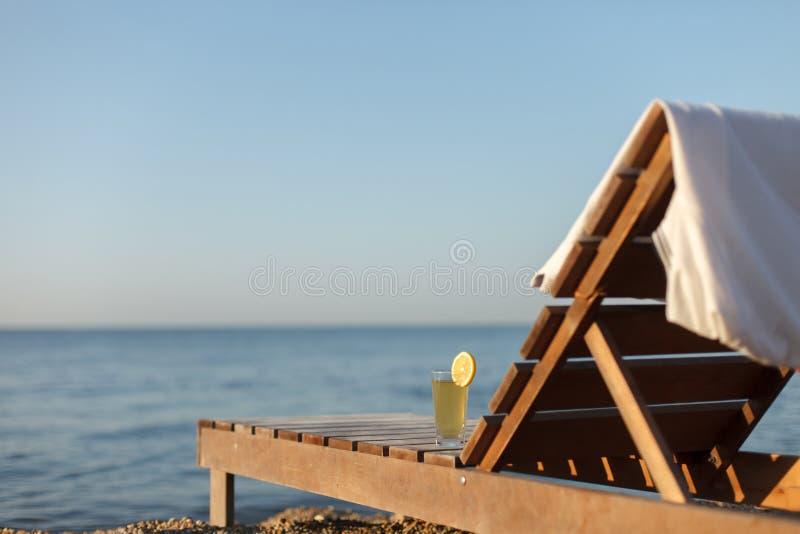 Sunbed con el polo y el vidrio de la bebida fría sobre él en la playa del mar fotos de archivo