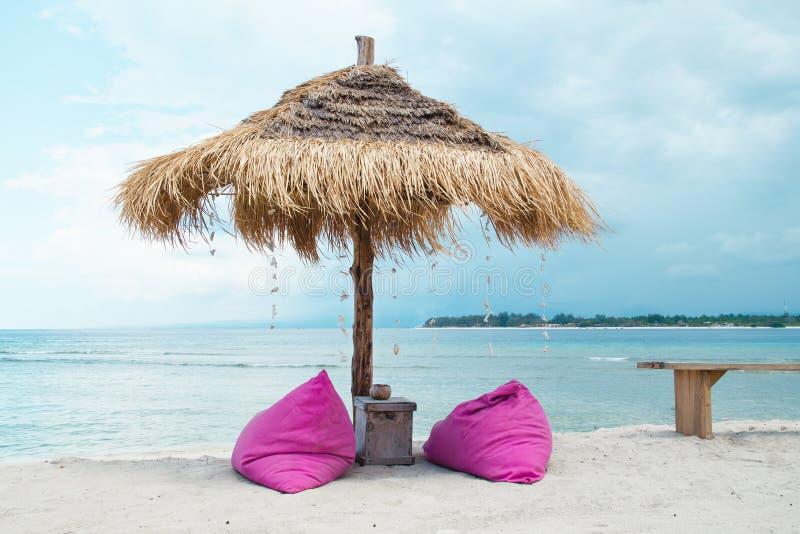Sunbed en paraplu op een tropisch strand - Voorraadbeeld stock afbeelding