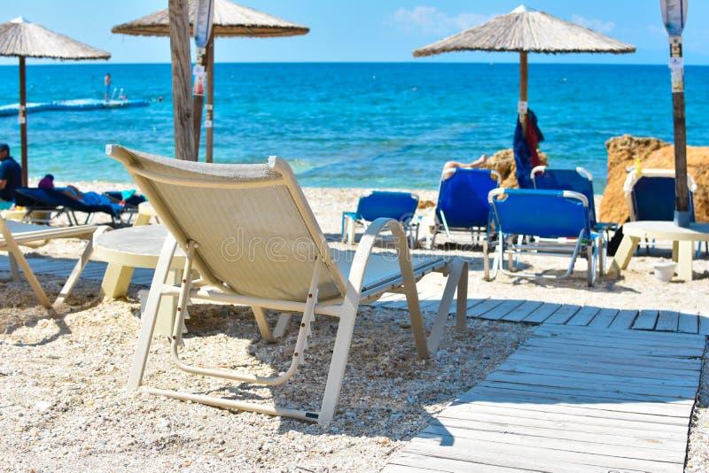 Sunbed i sanden vid stranden under paraplyet som vänder mot det blåa havet och klar himmel arkivfoto