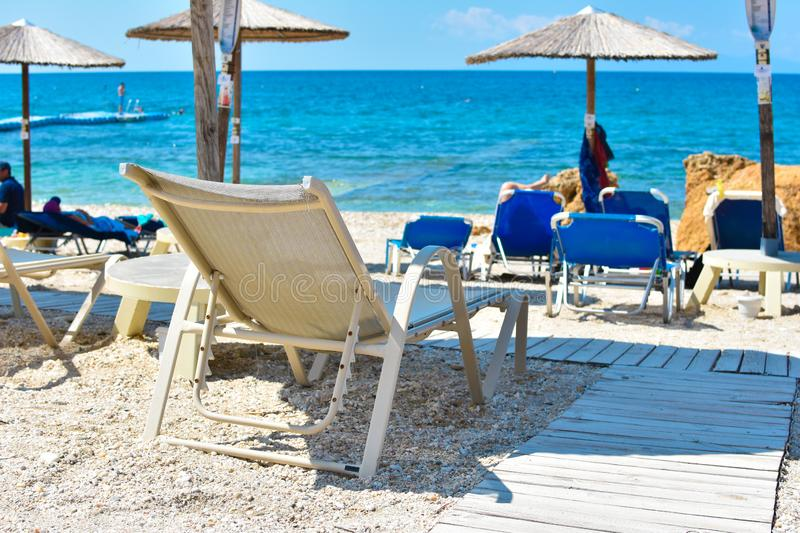 Sunbed in the sand by the beach under umbrella facing blue sea and clear sky stock photo