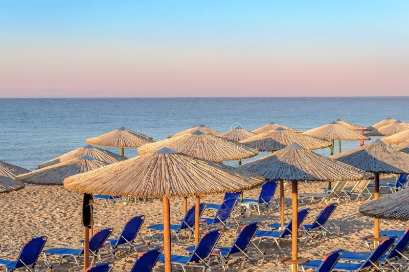 Sunbed, straw umbrella on beautiful rising sun beach background. Close royalty free stock images