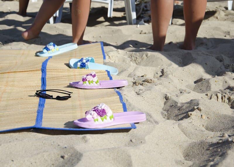 Sunbed z łupkami i okularami przeciwsłonecznymi na piasku plaża przeciw tłu garbnikować nogi zdjęcia stock