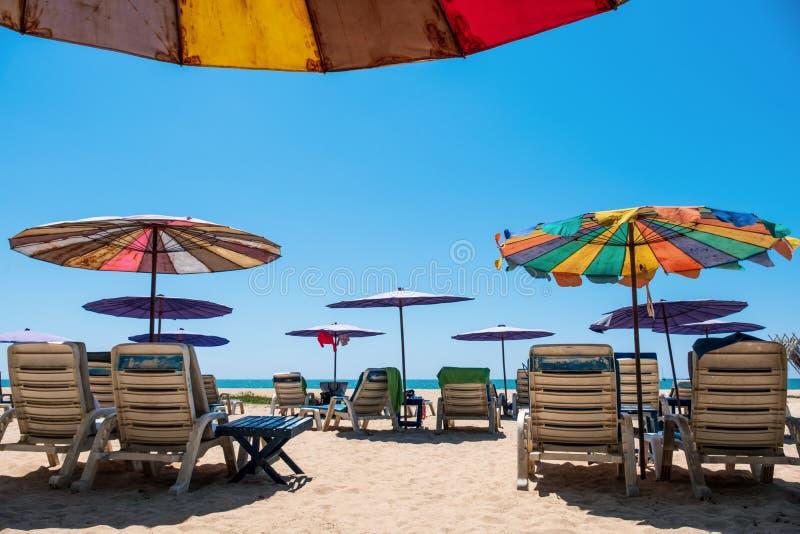 Sunbeds και ομπρέλες στην τροπική παραλία με το μπλε ουρανό στοκ εικόνες