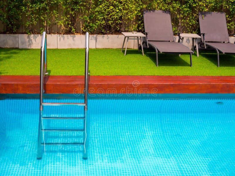 Sunbeds на зеленом стекле на открытом бассейне в саде стоковые изображения