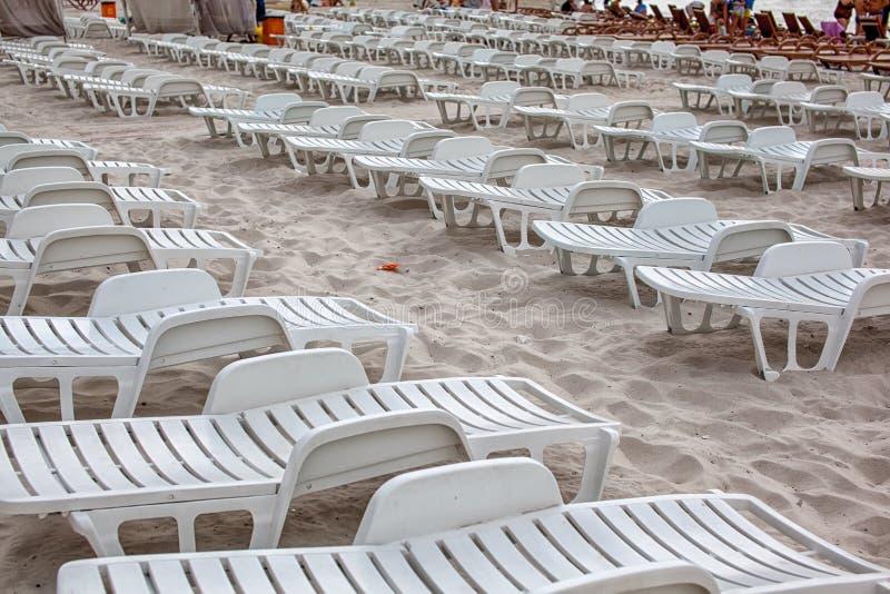 Sunbeds in buiten het seizoen Lege stoelen op zandig strand royalty-vrije stock foto's
