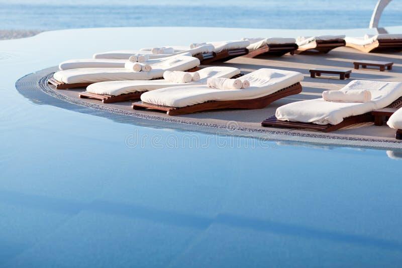 Sunbeds durch das Pool stockbild