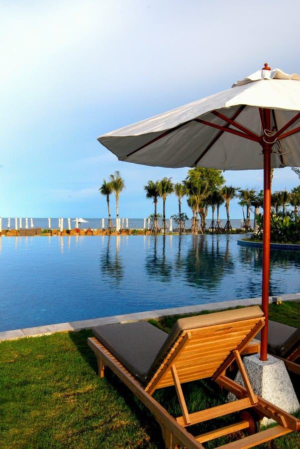 Sunbeds e guarda-chuvas de madeira na praia imagem de stock royalty free