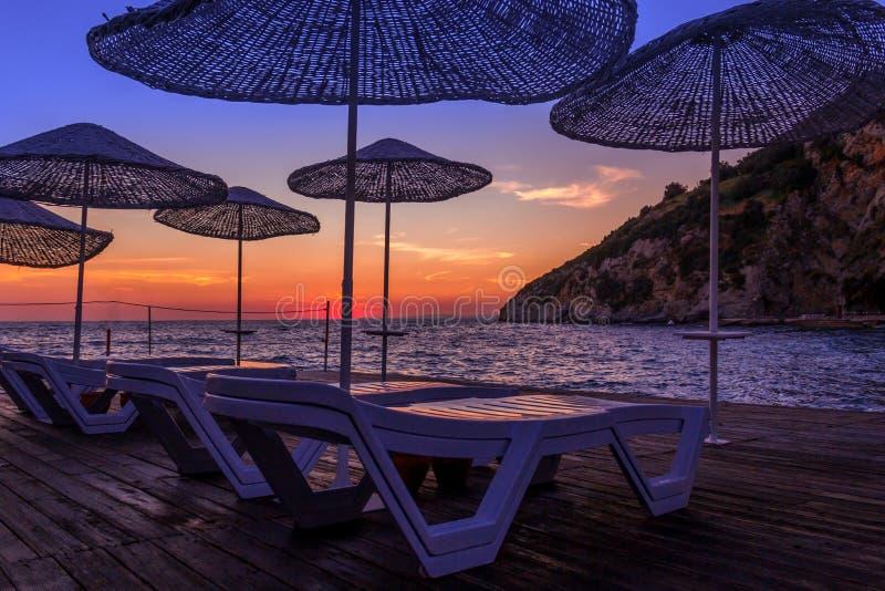 Sunbeds en paraplu's bij zonsondergang royalty-vrije stock fotografie