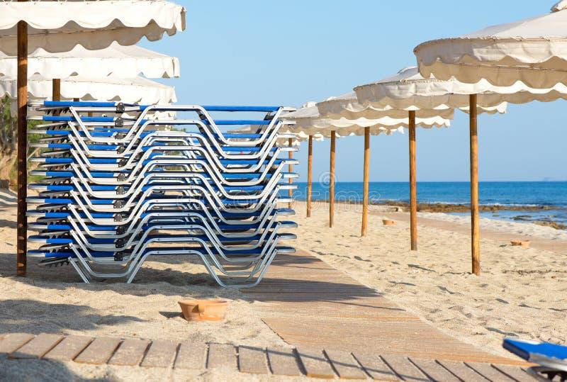 Sunbeds en paraplu's op het strand stock fotografie