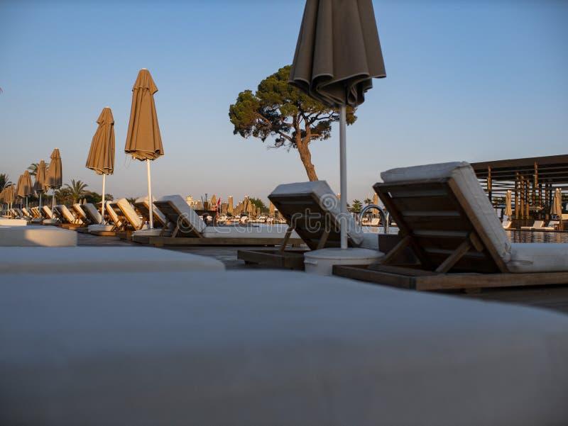 Sunbeds en van de paraplu's dichtbij toevlucht pool Zonbedden en paraplu's bij poolside stock afbeeldingen