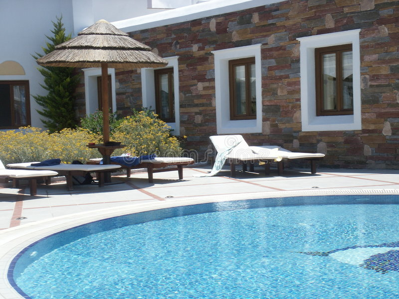 Sunbeds et hutte par la piscine photo libre de droits