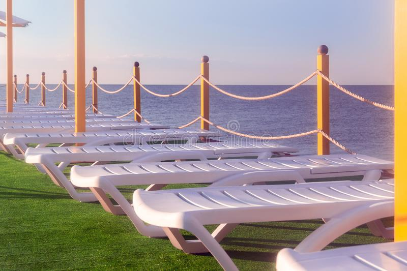 Sunbeds on the grass by the sea royalty free stock images