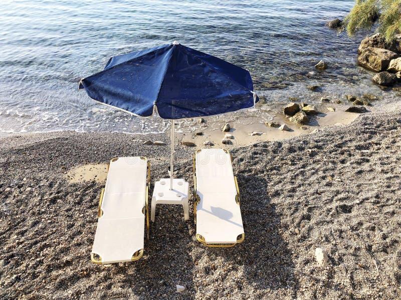 Sunbeds i parasol na piaskowatej plaży w lecie obrazy royalty free